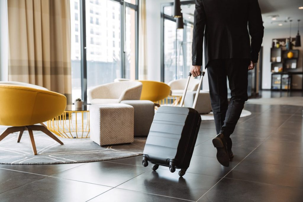 Man with suitcase walking through hotel lobby