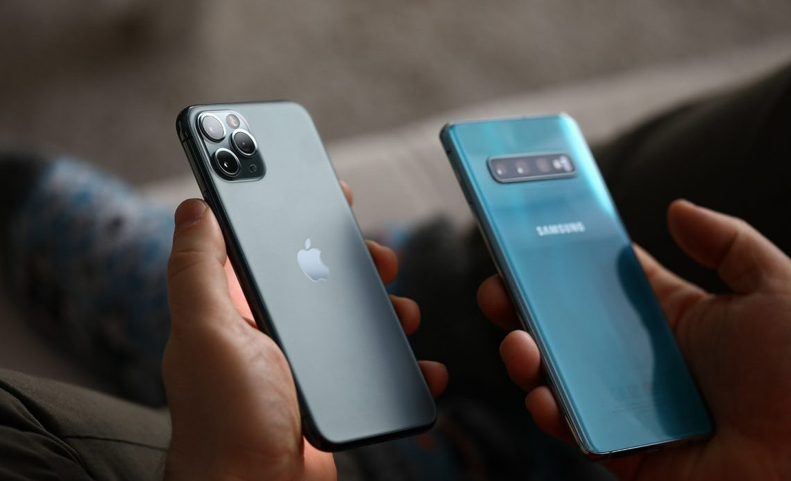 Male hand hold Apple iphone pro and samsung galaxy s 10