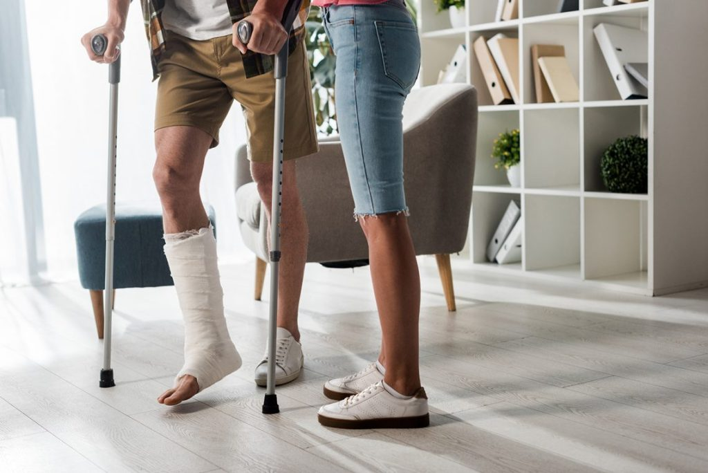 Woman supporting man using crutches. Plaster cast on leg.