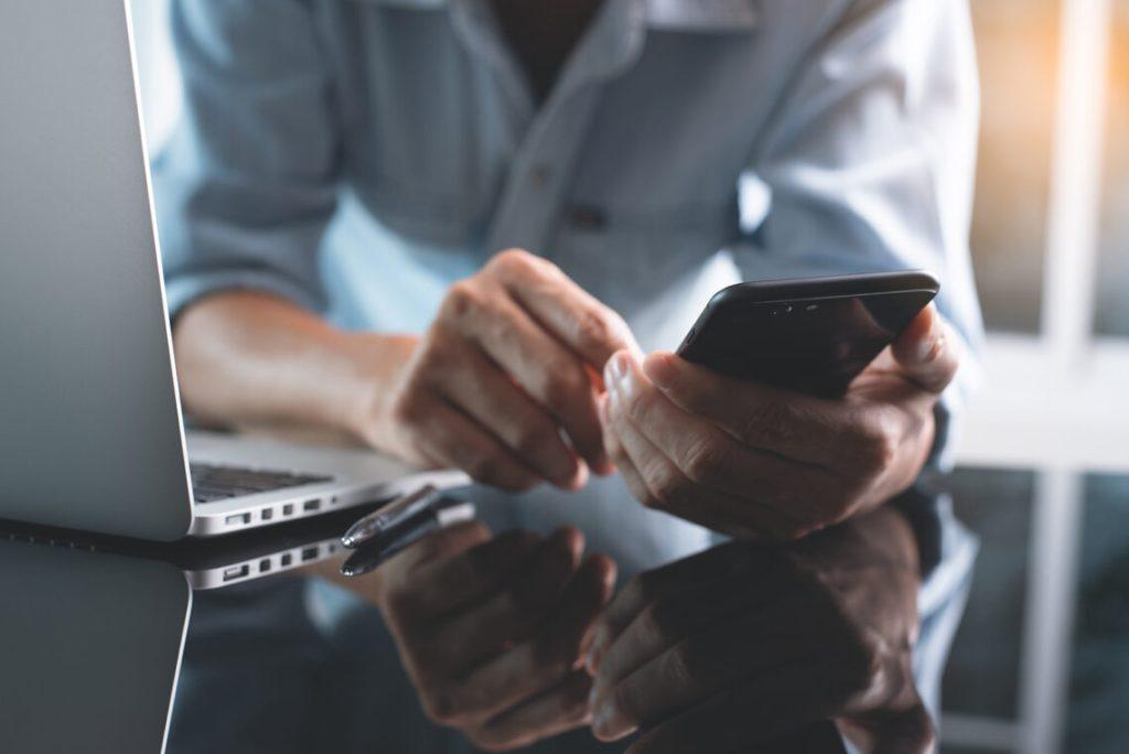 Man using mobile phone next to laptop