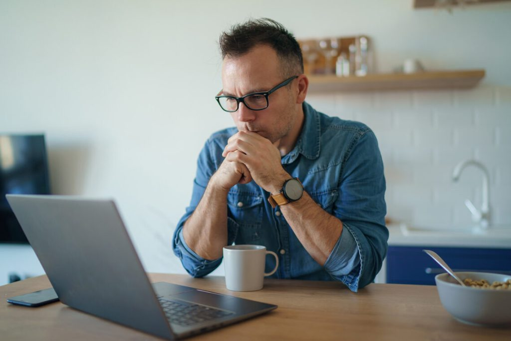 Man with laptop looking worried