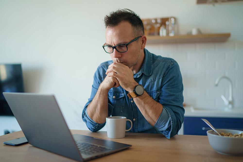 Worried man using laptop
