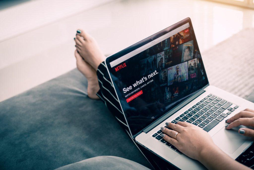 Woman using computer laptop and watching Netflix website.