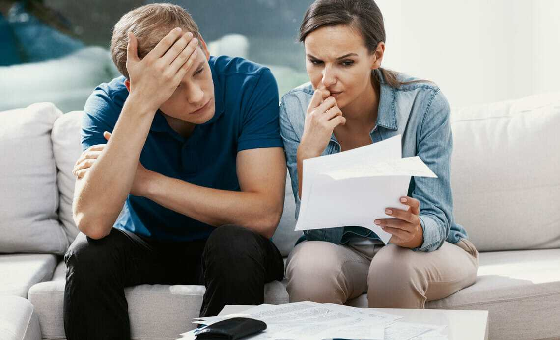 Couple sat on sofa looking stressed. Looking over bills with calculator
