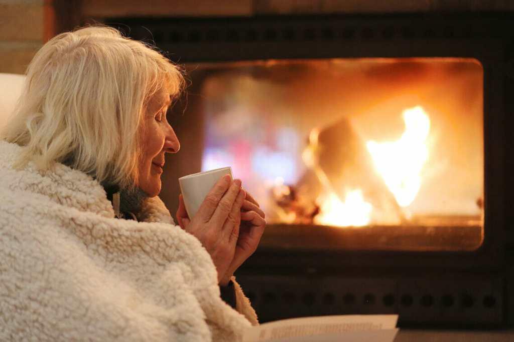 Elderly women keeping warm by fire