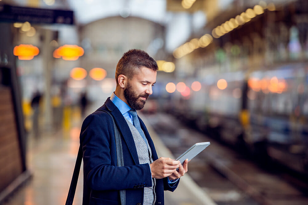 Business man with tablet waiting at train station platform