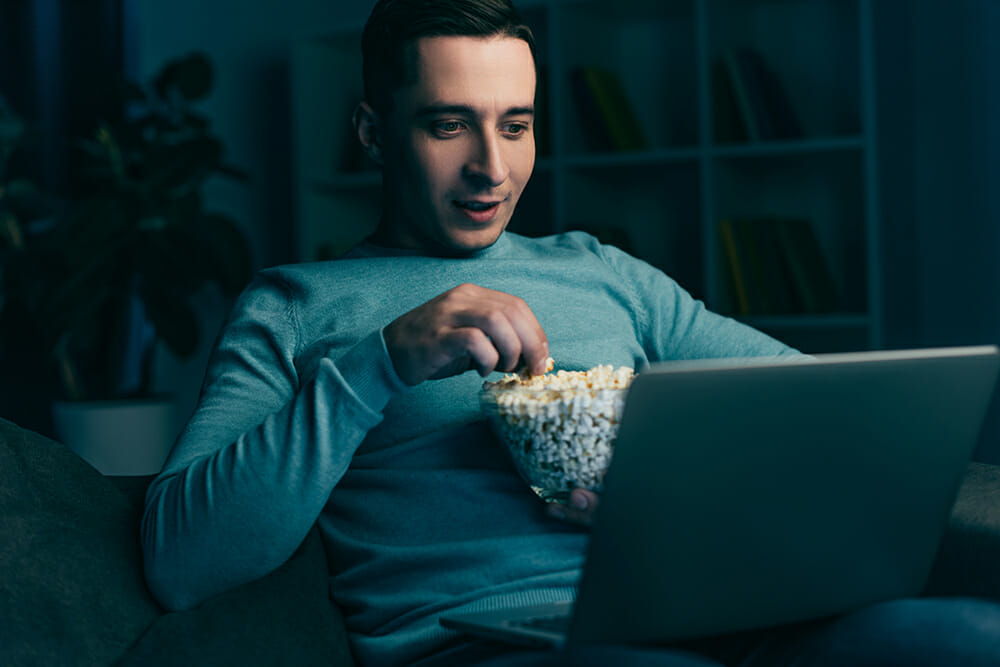 Man watching tv on laptop with popcorn