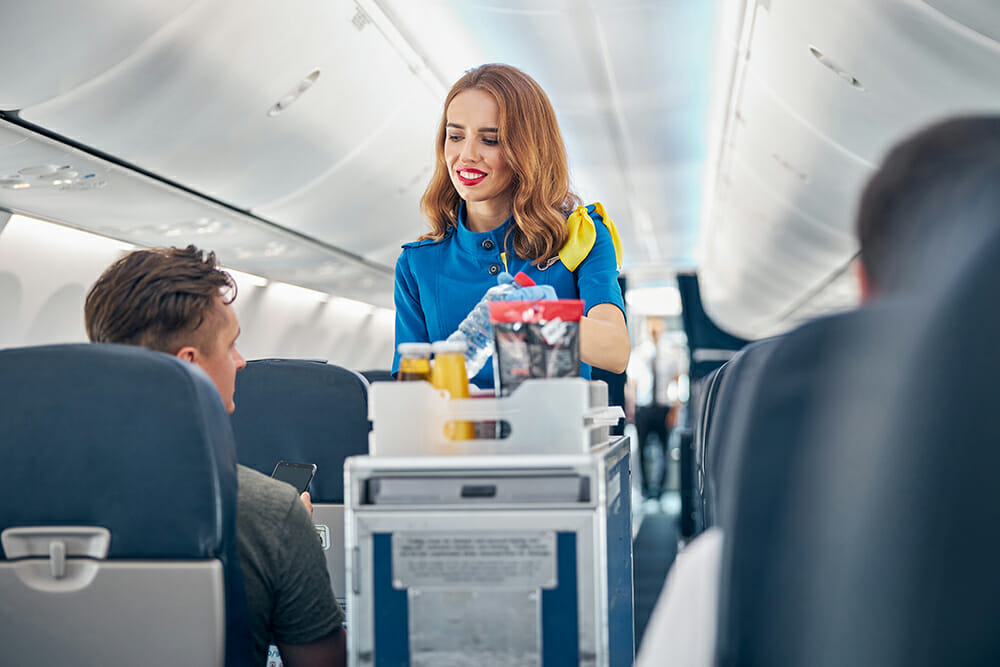 Flight attendant serving food and drinks to passengers on board