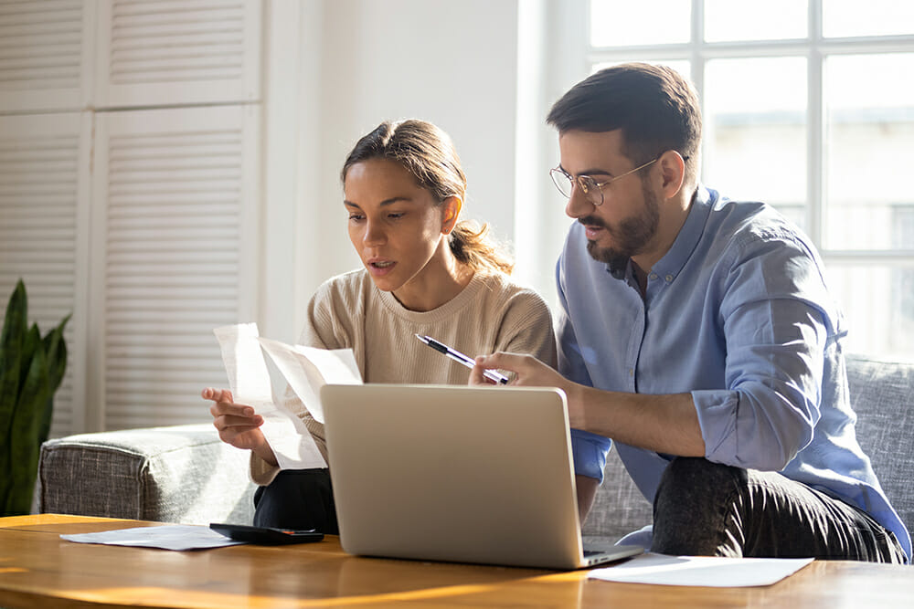 Stressed couple with laptop and paperwork