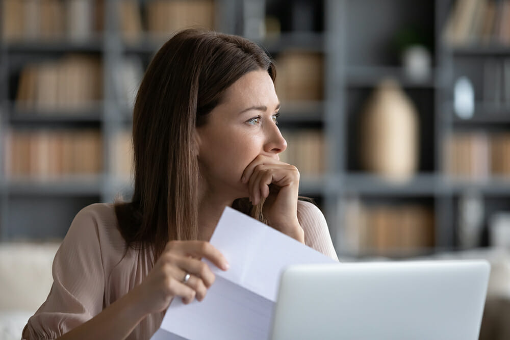 Stressed young woman holding paper document