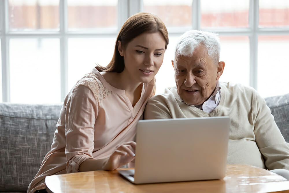 Women helping elderly man with computer laptop