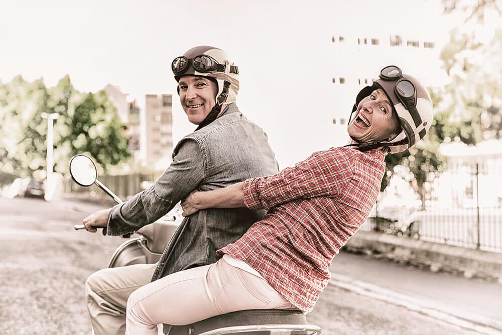 Retired elderly couple on moped