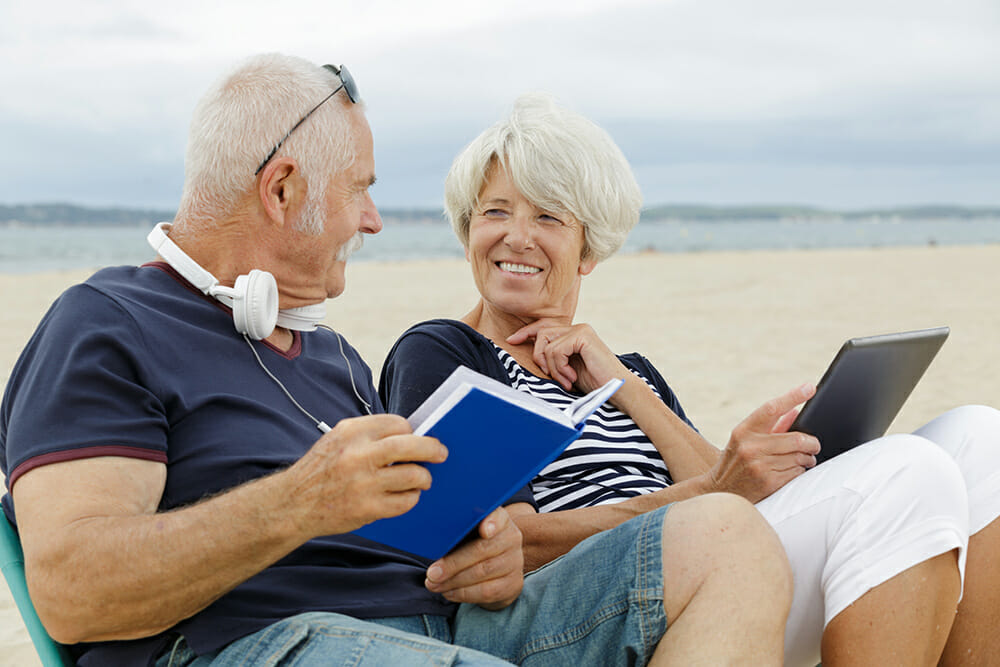 Elderly Couple sat chatting on the beach with book and ipad