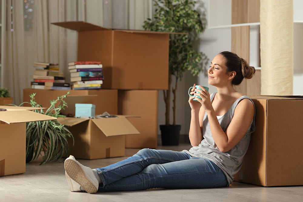 Women drinking from mug. Surrounded by packed boxes for moving home