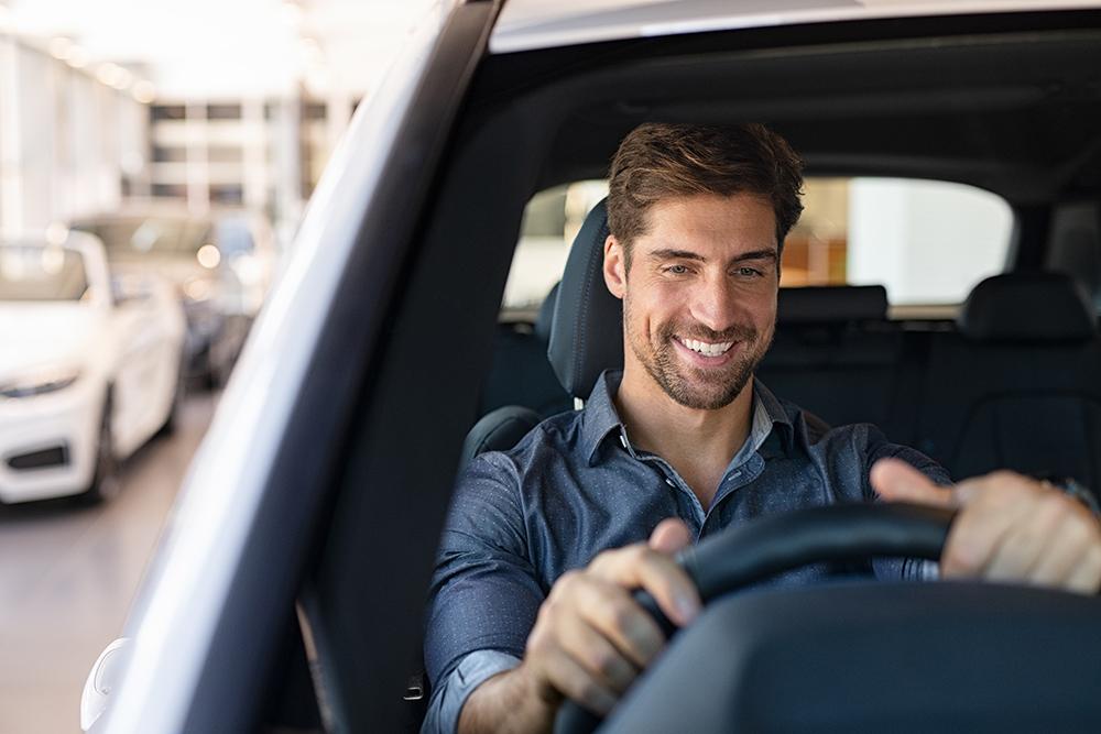 Man driving away in new car