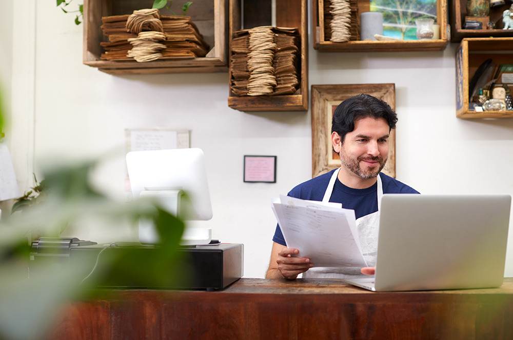 Man sat at desk with aptop. Man running small business