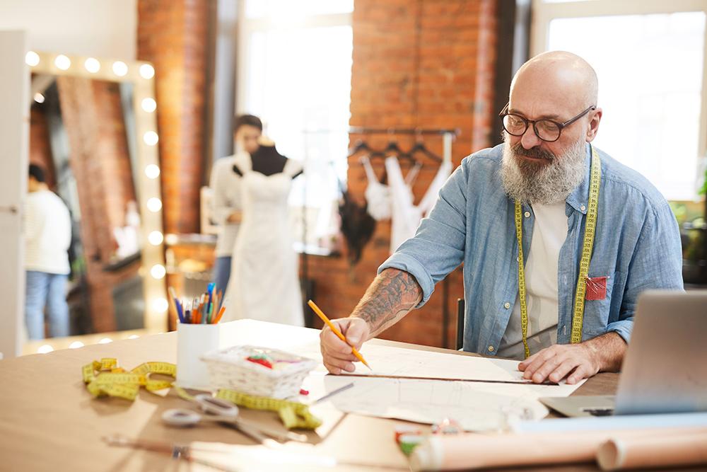 Man working on wedding dress designs