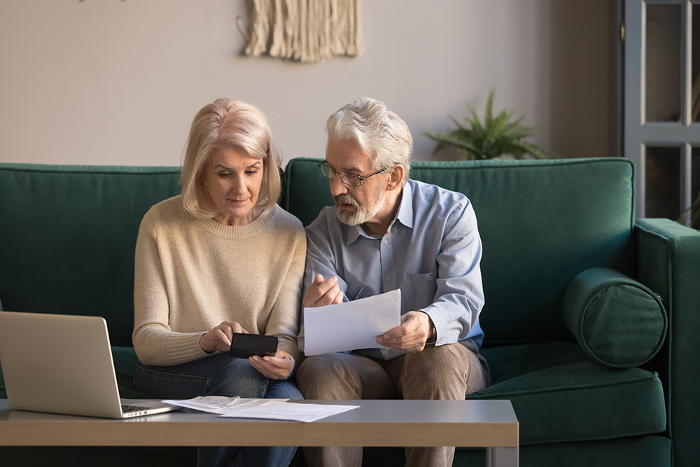 Elderly couple sitting on sofa looking over paper work
