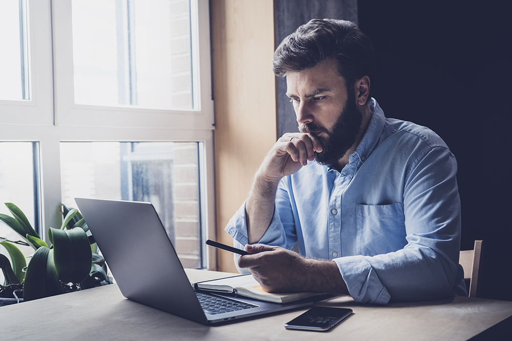 Man with blue shirt and beard thinking whilst holding mobile phone and using laptop