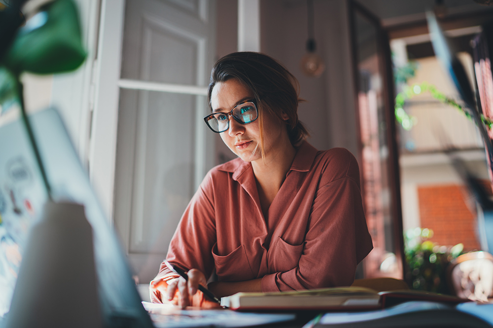 Women with brown hair and glasses sat at desk working on laptop