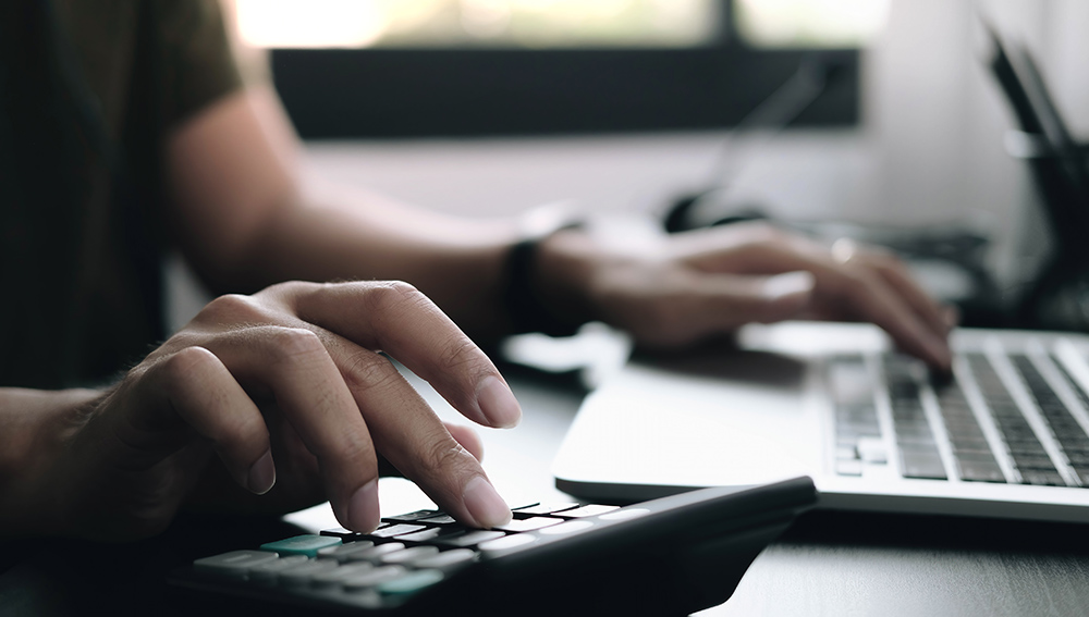 Arms and hands of person using laptop and calculator