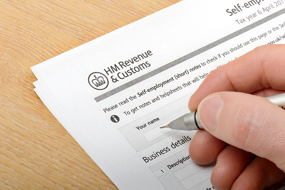 Filling in with a pen HMRC self employment form