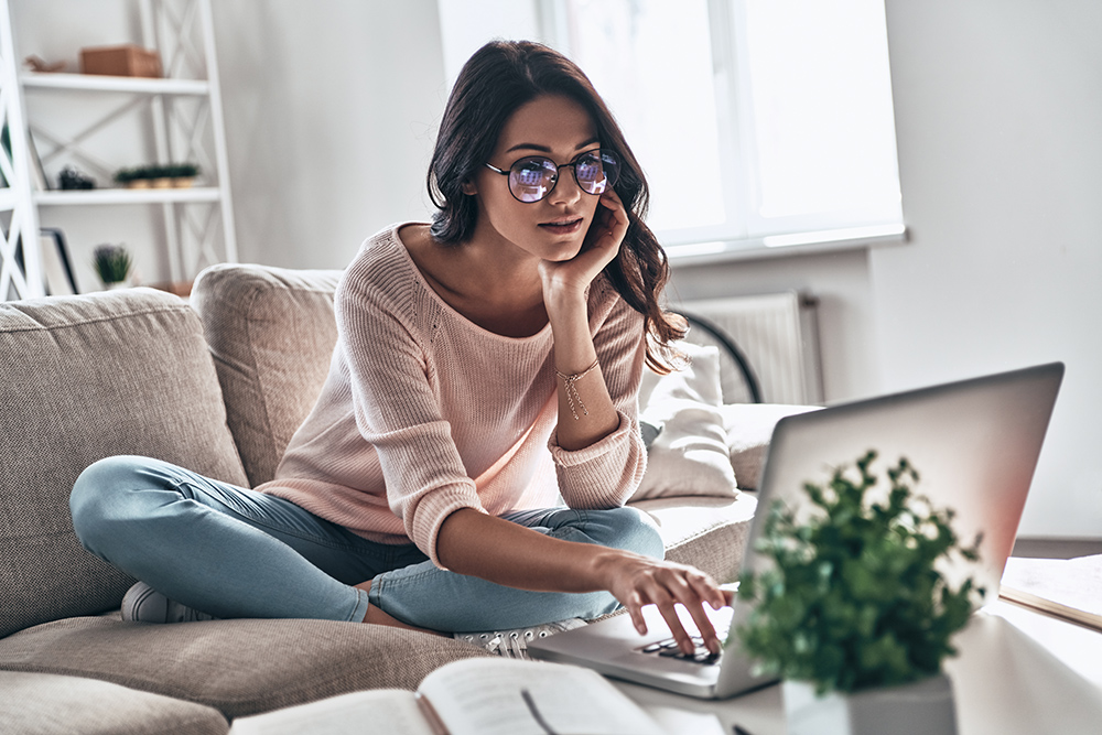 Women with brown hair and glasses sat on sofa using laptop