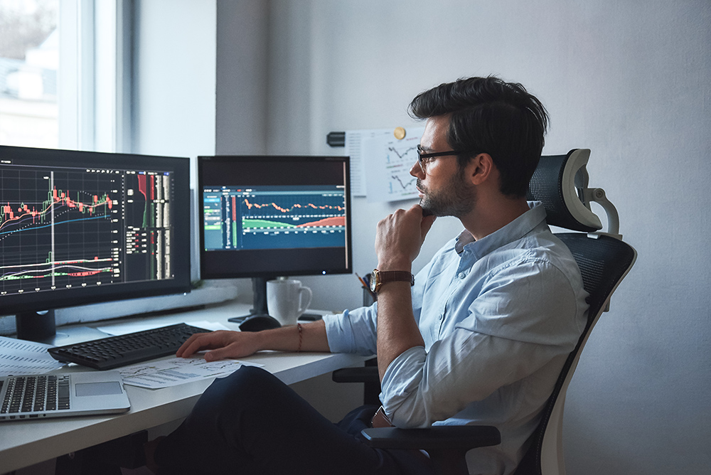 Smart man looking at multiple computer screens with stock market charts