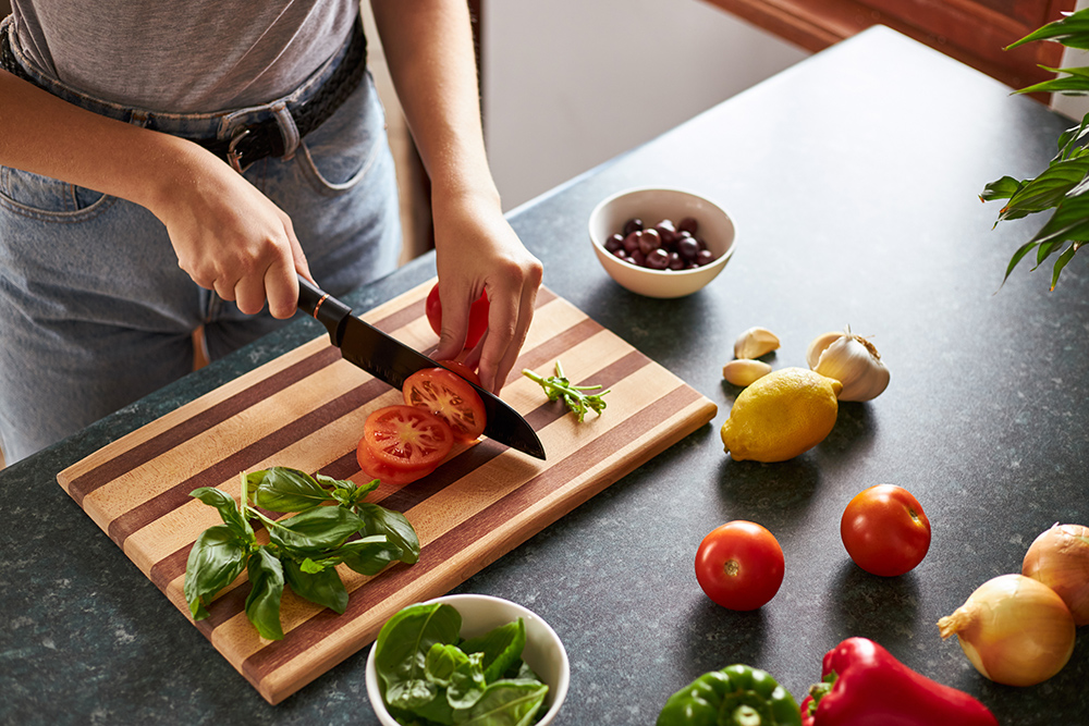Meal Prepping. Cutting vegetables with a sharp knife on a wooden chopping board.