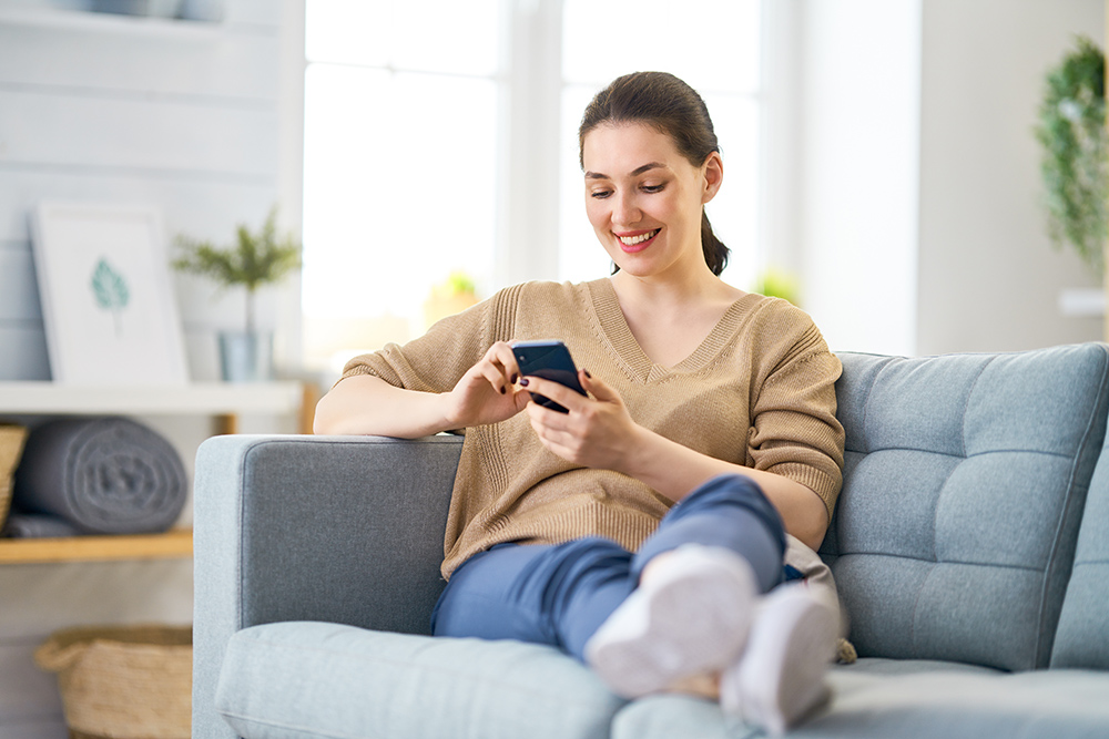 Women relaxed sitting on sofa using phone