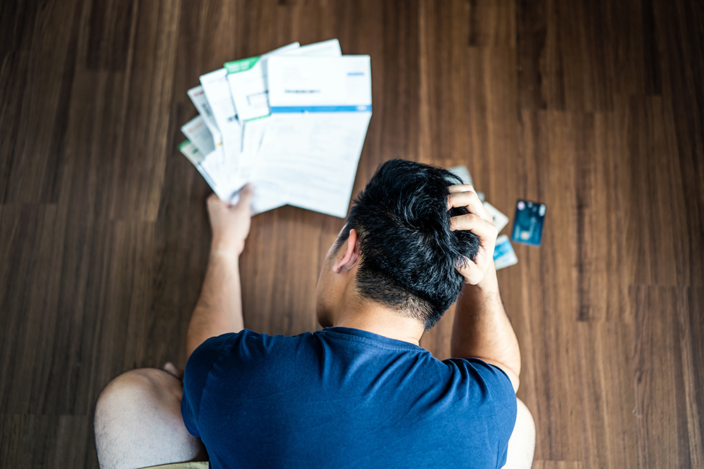 Man with his head in his hands looking at a handfull of offical letters