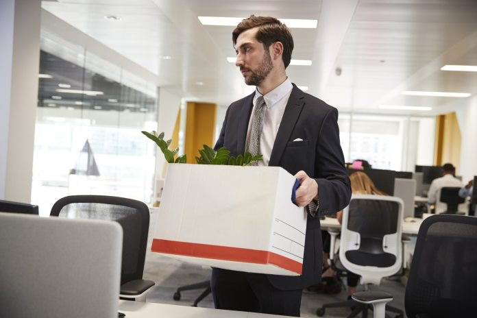 Fired male employee holding box of belongings in an office