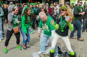 Photo by Aaron Warnick | Photo Editor. Parade-goers dance, drink and party in the streets of Pittsburgh during the 114th annual St. Patrick's Day Parade.