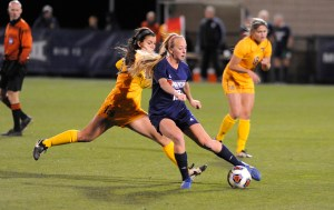 Courtesy of Athletic Department Freshman midfielder Abby Losco attempts to shake off a WVU defender in the Dukes' 4-0 loss to the Mountaineers last Friday night. This was Duquesne's first NCAA tournament appearance.
