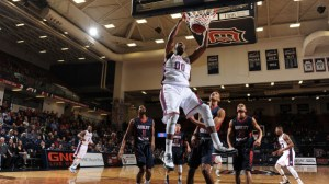 Photo from GoDuquesne. Junior Center Darius Lewis slams down a two-handed dunk in Saturday's win over Robert Morris.