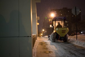 Photo by Seth Culp-Ressler | Features Editor. A snowplow-equipped tractor clears snow in front of the Union early Saturday. Twenty-five employees worked to ready campus for the day.