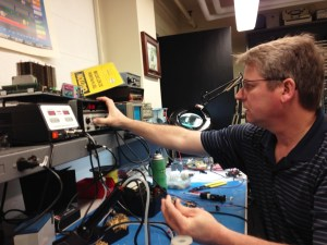 Courtesy of Don Maue   Dan Bodnar, manager of instrument maintenance in the Bayer school, tests a broken capacitor taken from the carillon bell control unit in the Administration Building.
