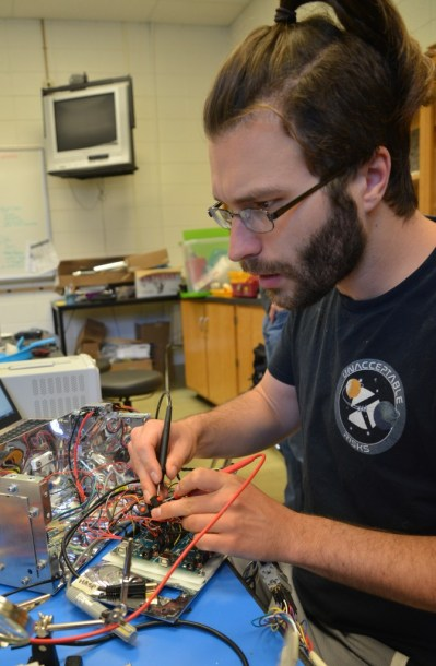 Durham Tech student Dan Koris wires a sensor assembly to make sure it functions safely and reliably during thermal testing at the Durham Tech main campus in May.