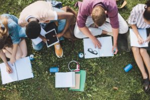 Students clustered together while studying outdoors.