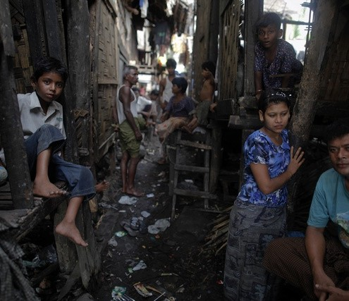 Myanmar Rohingya people pass the time at their slum near the sea in the town of Sittwe