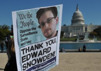 Demonstrators hold placards supporting former US intelligence analyst Edward Snowden during a protest against government surveillance on 26 October 2013 in Washington, DC. (PHOTO: AFP)