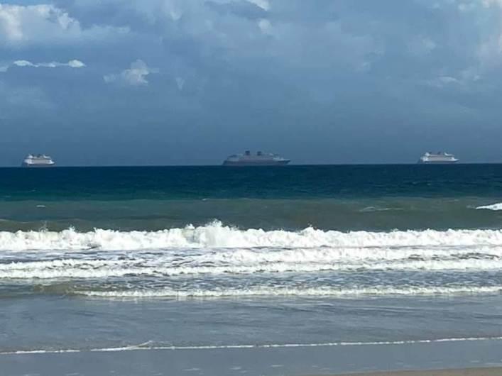 Disney Cruise Line ship on the horizon from the beach