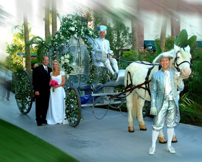 Husband and wife standing with Cinderella's carriage.