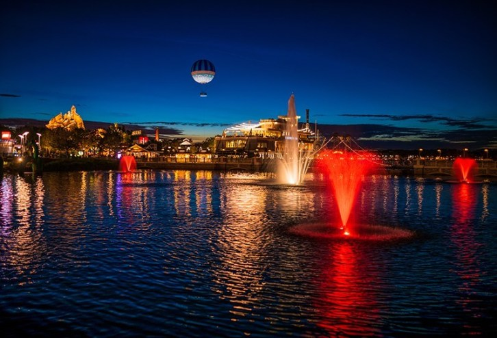 Disney Springs at night with glowing fountains of colored light and an air balloon in the sky.
