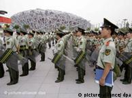 Chinese soldiers standing in a group with the Olympic stadium in the background.