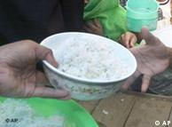 A bowl of rice is being handed from an adult hand to a child's