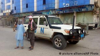 Taliban fighters pose for a photo next to a UN vehicle which they used in Kunduz, Afghanistan after taking parts of the city