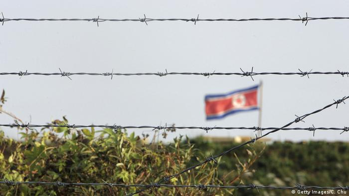 Barbed wire in front of a North Korean flag (Getty Images/C. Chu)