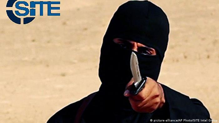 IS militant Jihadi John, dressed in all black with his face masked, except for his eyes, and pointing a knife at the camera.