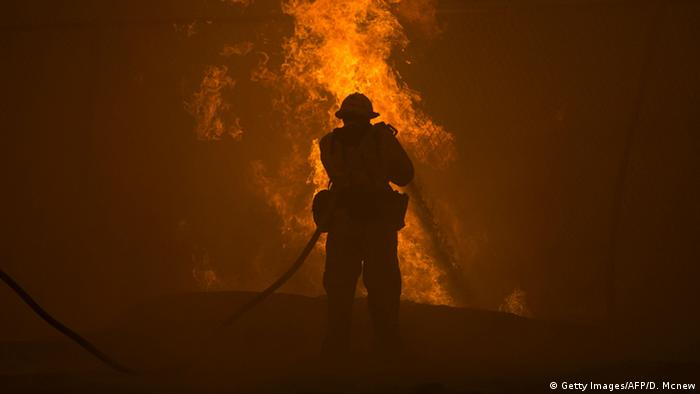 A firefighter hoses down burning pipes near a water tank at the Sand Fire on July 23 2016 near Santa Clarita, California (Photo: Getty Images/AFP/D. Mcnew)